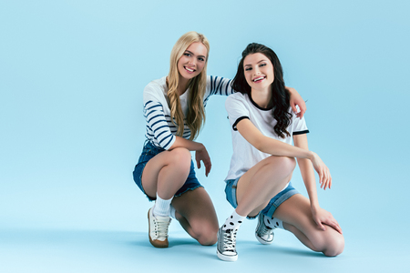 Cute girls squatting and embracing on blue background Reklamní fotografie