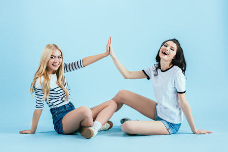 Joyful girls sitting on floor and touching hands on blue background