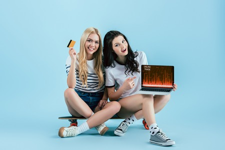 Blissful friends on longboard holding credit card and laptop with online trade website on screen on blue background Reklamní fotografie