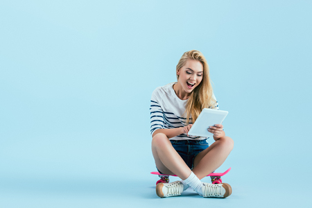 Excited girl using digital tablet while sitting on longboard on blue background Stock Photo