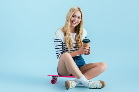 Beautiful girl sitting on longboard with cup of coffee on blue background Stockfoto