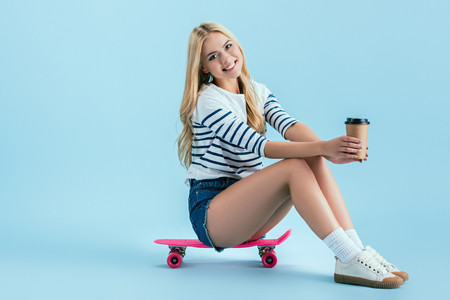 Smiling girl with cup of coffee sitting on longboard on blue background
