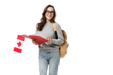 female student looking at camera and holding canadian flag with notebook isolated on white Stock fotó