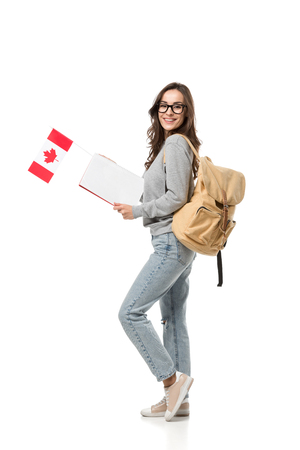 female student with backpack holding canadian flag and notebook isolated on white