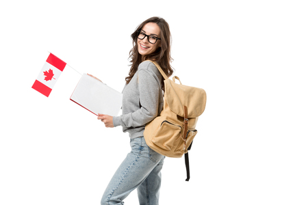 happy female student with backpack holding canadian flag and notebook isolated on white