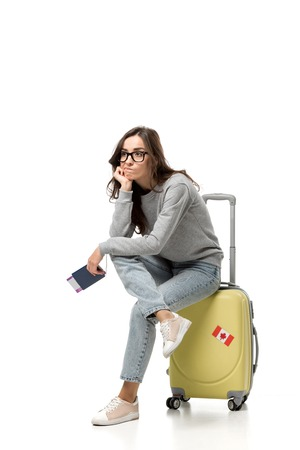 pensive woman sitting on suitcase with passport and air tickets isolated on white, travel concept Stock Photo