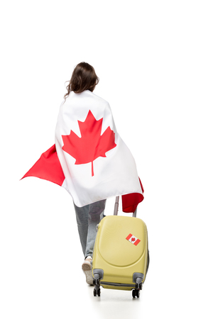 back view of woman covered in canadian flag with suitcase isolated on white, travel concept Stock Photo