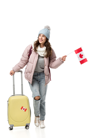 female student in winter clothes with suitcase holding canadian flag isolated on white Banque d'images - 118408573
