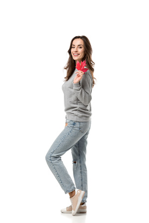 smiling woman in casual clothes holding maple leaf and looking at camera isolated on white