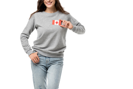 partial view of smiling woman with canadian flag badge isolated on white
