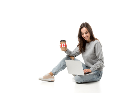 smiling woman using laptop and holding coffee cup with canadian flag sticker isolated on white Imagens