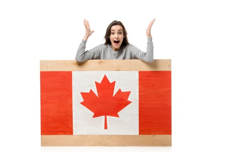 surprised woman gesturing with hands behind wooden board with canadian flag isolated on white Stock Photo