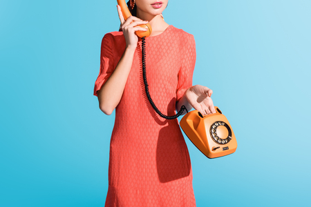 cropped view of woman in living coral dress posing with rotary telephone isolated on blue