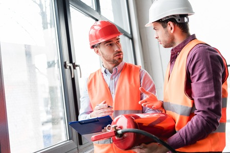 fireman in helmet looking at coworker while talking and holding red extinguisher