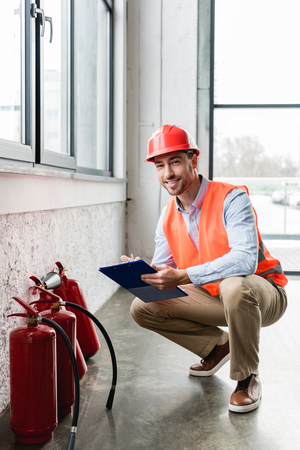 cheerful fireman in helmet holding clipboard and pen while looking at camera near extinguishers