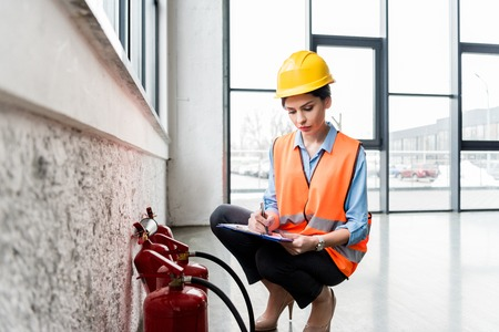 beautiful firefighter in helmet writing on clipboard while checking extinguishers Foto de archivo