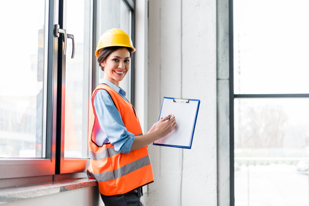 cheerful female firefighter in helmet and uniform holding clipboard with blank paper