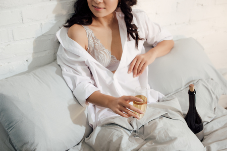 cropped shot of beautiful girl in bra and white shirt holding glass of wine in bed 免版税图像