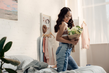 happy attractive asian girl kneeling on bed and holding beautiful flower bouquet 版權商用圖片