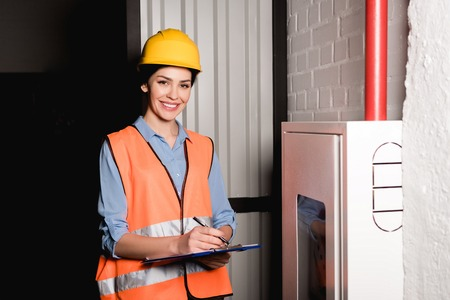 cheerful female firefighter standing near fire panel and writing on clipboard Foto de archivo