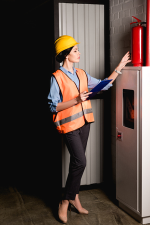 beautiful female firefighter standing near fire panel and looking at red extinguisher Reklamní fotografie