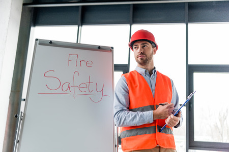 handsome firefighter in helmet holding clipboard and pen while standing near white board with fire safety lettering Archivio Fotografico - 118407553