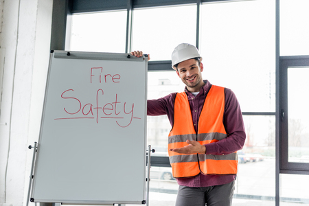 cheerful firefighter in helmet gesturing while standing near white board with fire safety lettering Archivio Fotografico - 118407572