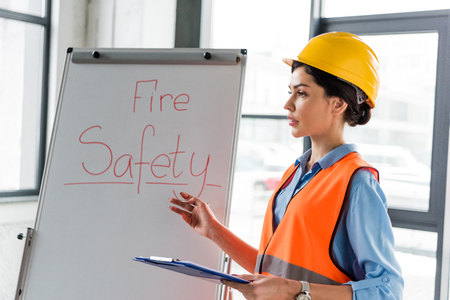 female firefighter in helmet holding clipboard and pen while talking near white board with fire safety lettering
