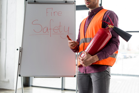 cropped view of fireman holding red extinguisher while standing near white board with fire safety lettering