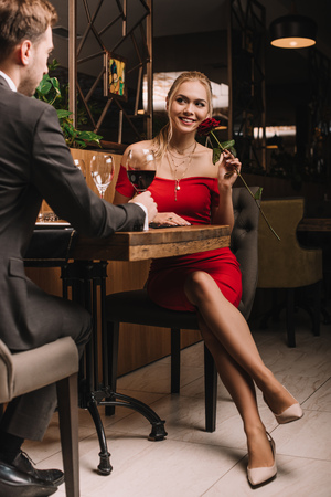 attractive girl sitting with red rose and looking at boyfriend in restaurant