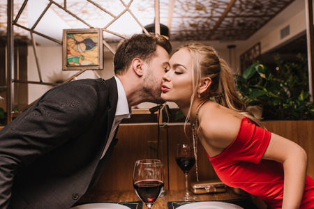 attractive girl kissing cheek of man in restaurant on valentines day Stok Fotoğraf