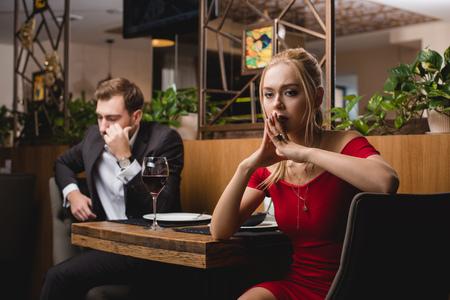selective focus of offended woman sitting near boyfriend in restaurant Reklamní fotografie