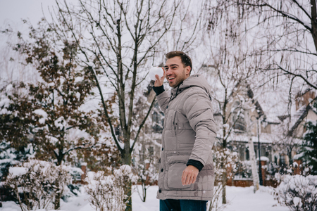 cheerful man throwing snowball in winter