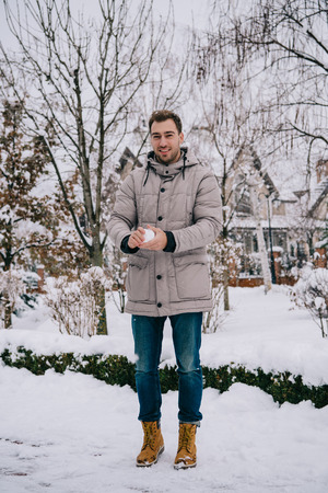 cheerful man holding snowball in hands in winter