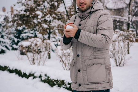 cropped view of man holding snowball in hands in winter Stok Fotoğraf
