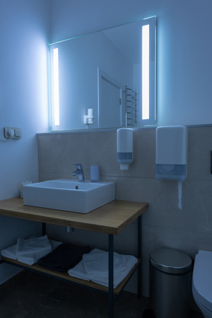 hotel bathroom with washstand and towels with neon light on mirror