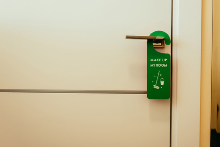 green sign with make up my room lettering on door handle, cleaning service