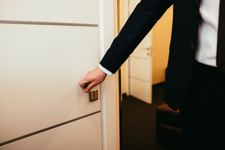 partial view of man holding door handle and coming into hotel room