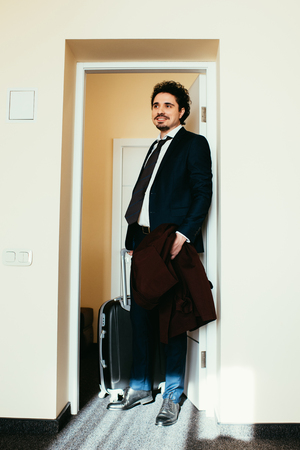 businessman in suit with travel bag in hotel room Stock Photo