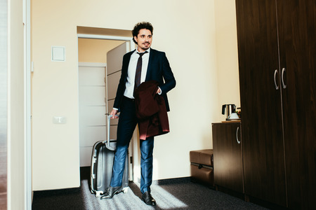 businessman in suit with suitcase in hotel room