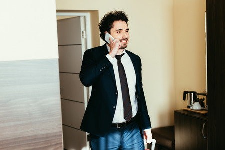 businessman talking on smartphone during business trip in hotel room Stockfoto
