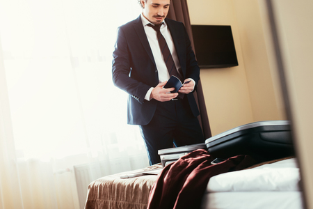 adult businessman holding passport in hotel room with suitcase on bed Zdjęcie Seryjne