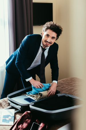 smiling businessman with clothes in travel bag on bed in hotel room