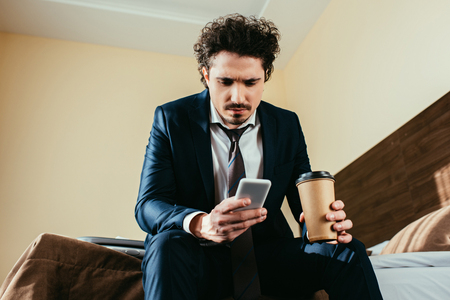 upset businessman using smartphone and holding disposable cup of coffee in hotel room Stockfoto