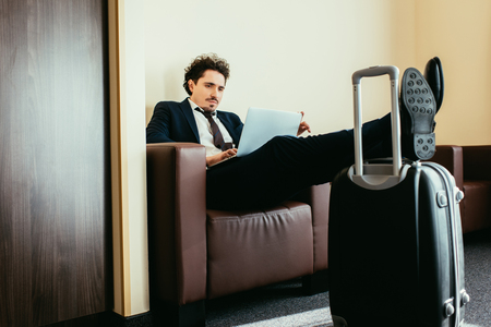 businessman teleworking on laptop with legs on travel bag in hotel room