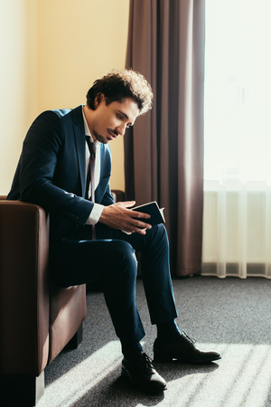 businessman holding passport and sitting in hotel room