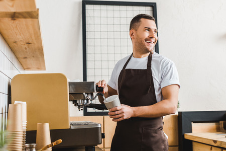handsome barista holding cup and making coffee with machine in coffee house Banque d'images - 118426713