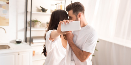 couple in white clothes taking selfie on smartphone at home Stock fotó