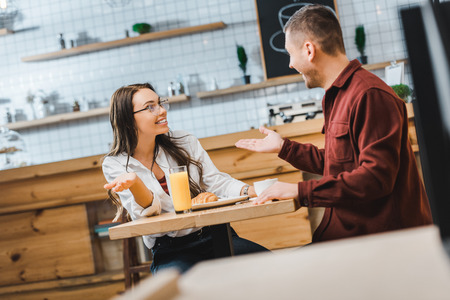 selective focus of attractive brunette woman with glass of juice and handsome man with cup of coffe sitting and smiling at table in coffee house