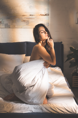 beautiful sensual woman covering body with duvet and sitting on bed at home 写真素材